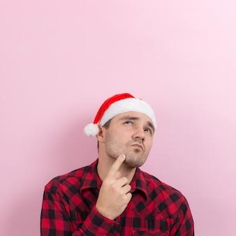 Emozioni sul viso, pensieroso, riflesso, piano, idea. un uomo in un coniglio plaid e un cappello rosso di natale