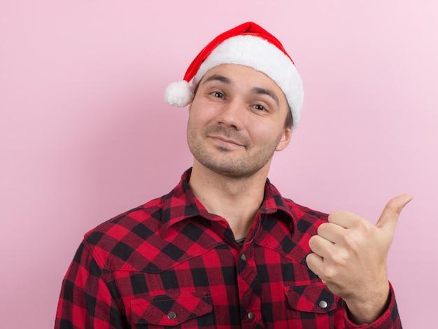 Emozioni sul viso, sorriso, gioia. un uomo in un coniglio plaid e un cappello rosso di natale