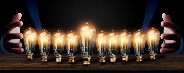 Energia di idea dell'innovazione di affari e di successo con la lampadina sulla tavola e sull'uomo d'affari di legno nel tono scuro, riuscito capo creativo e concetto di invenzione