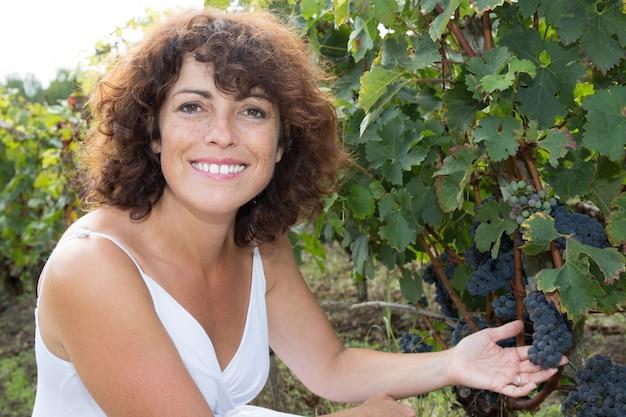Enologo della donna con l'uva in una vigna