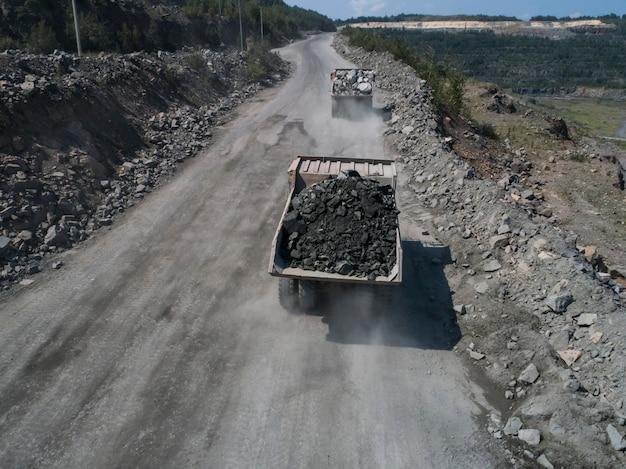 Enorme autocarro con cassone ribaltabile industriale in una cava di pietra caricata trasportando marmo o granito sparato da un colpo di drone