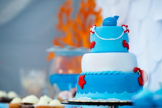 Enorme torta di compleanno blu e bianca con granchio dolce, pesce, stelle marine e balena divertente in cima