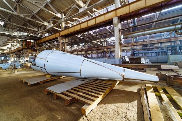 Enorme tubo sullo sfondo della moderna fabbrica di ingegneria. una grande costruzione sul supporto di legno all'interno della fabbrica.