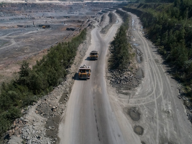 Enormi dumper industriali in cava di pietra caricati granito sparato drone top shot