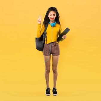 Ente completo della ragazza dello studente dell'adolescente con capelli ricci che sorride e che mostra il segno di vittoria con la b