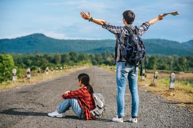 Entrambi i turisti maschi stanno in piedi e alzano le mani su entrambi i lati. turiste che si siedono sulla strada