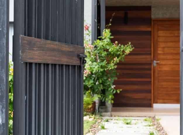 Entrata di recinzione della porta dello stell nero a casa con il blocchetto del cemento e la passerella bianca delle pietre