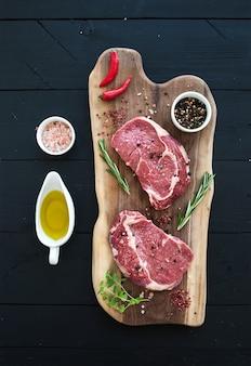 Entrecote e condimenti crudi della bistecca di ribeye della carne fresca sul tagliere sopra la tavola di legno scura.