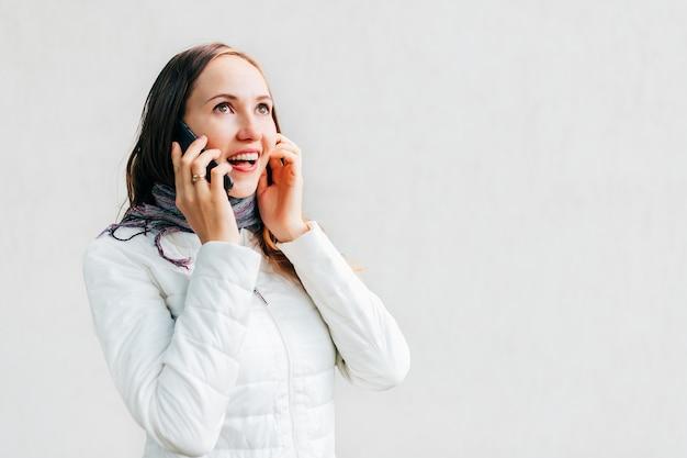 Entusiasta giovane donna caucasica in giacca bianca parla al telefono cellulare. buone notizie.