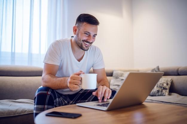 Entusiasta uomo caucasico bello in pigiama utilizzando il computer portatile e bere caffè mentre era seduto sul divano nel soggiorno in mattinata