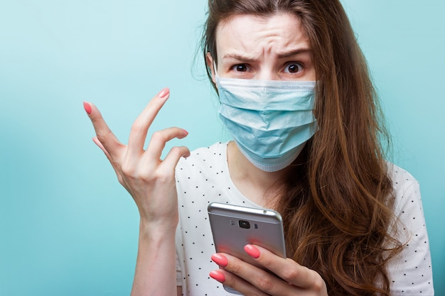 Epidemia di coronavirus. una ragazza in una maschera medica usa e getta e abiti da ospedale detiene uno smartphone in mano. indignato, arrabbiato, nervoso a causa di notizie scioccanti