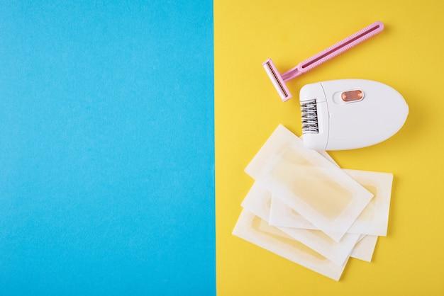 Epilatore, rasoio e strisce di cera su blu e giallo