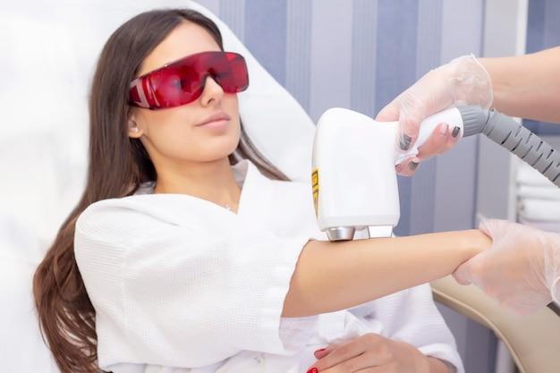 Epilazione laser e cosmetologia. la donna si toglie i capelli dal braccio con un laser. procedura di depilazione in cosmetologia. epilazione laser e cosmetologia. concetto di cosmetologia e spa