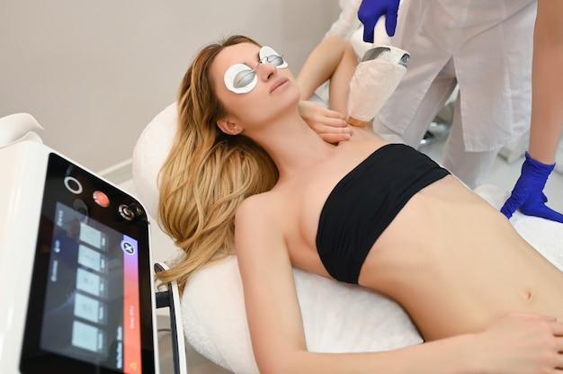 Epilazione laser e cosmetologia nel salone di bellezza. procedura di depilazione epilazione laser, cosmetologia, spa e concetto di epilazione. bella donna bionda che ottiene capelli che rimuovono sulle ascelle