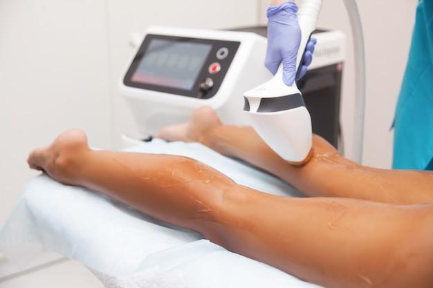 Epilazione laser e cosmetologia nel salone di bellezza. procedura di depilazione epilazione laser, cosmetologia, spa e concetto di epilazione. bella donna che ottiene rimozione dei capelli sulle gambe