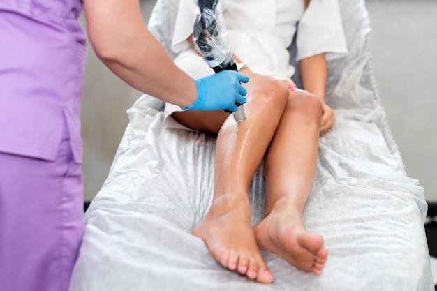 Epilazione laser su belle gambe femminili presso la clinica di bellezza. procedura di cosmetologia per la depilazione.