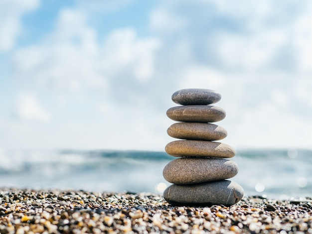 Equilibrio di pietre sulla spiaggia con copia spazio per testo o design. piramide di pietre come zen, armonia, concetto di equilibrio