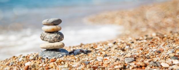 Equilibrio di pietre sulla spiaggia, giornata di sole