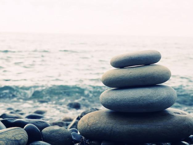 Equilibrio, tranquillità, pietre di diverse dimensioni formano una piramide, piramide di pietre sulla spiaggia di ciottoli che simboleggia stabilità, zen, armonia, equilibrio. profondità di campo
