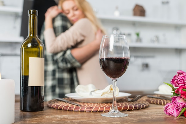 Equipaggi abbracciare con la donna vicino alla tavola con la bottiglia ed il bicchiere di vino