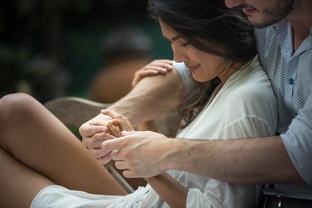 Equipaggi abbracciare e tenere l'anello di cerimonia nuziale per la fabbricazione della proposta di matrimonio sorpresa con le donne.