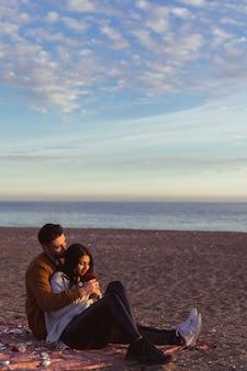 Equipaggi abbracciare la donna sul copriletto sulla riva di mare sabbiosa