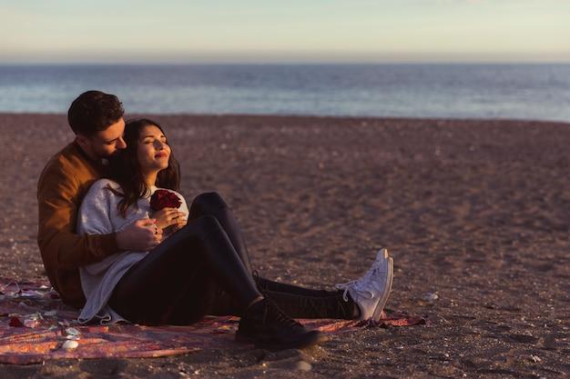 Equipaggi abbracciare la donna sul coverlet sulla riva di mare