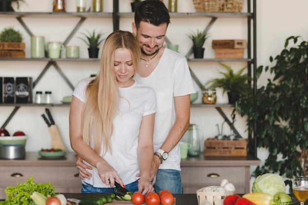 Equipaggi abbracciare la sua amica che taglia le verdure sul contatore di cucina