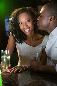 Equipaggi baciare una donna mentre mangiano il champagne al contatore della barra nella barra