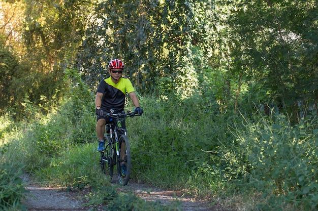 Equipaggi con il guanto del casco per sicurezza che guida una bicicletta alla strada della campagna lungo una foresta