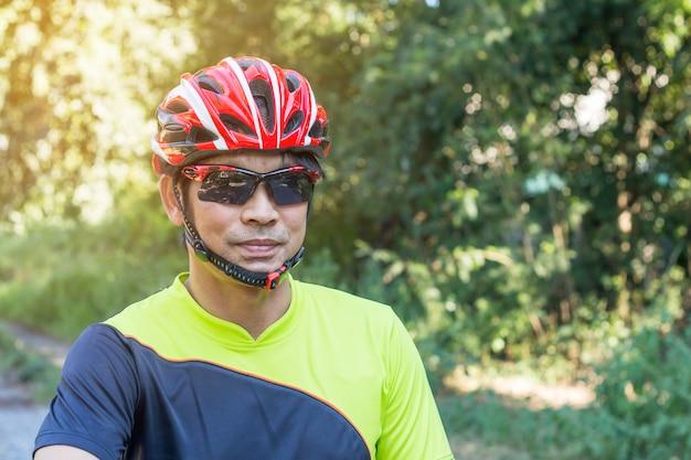 Equipaggi con il guanto del casco per sicurezza guidando una bicicletta alla strada della campagna lungo una foresta, guida del paese trasversale
