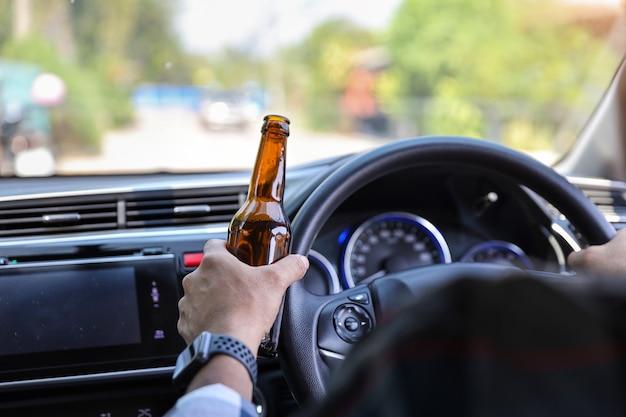 Equipaggi condurre l'automobile e la tenuta della bottiglia dell'alcool in un'altra mano mentre sulla strada