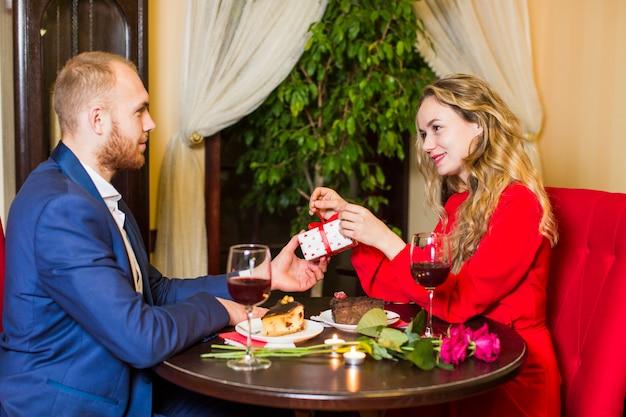 Equipaggi dare il contenitore di regalo alla donna graziosa alla tavola in ristorante