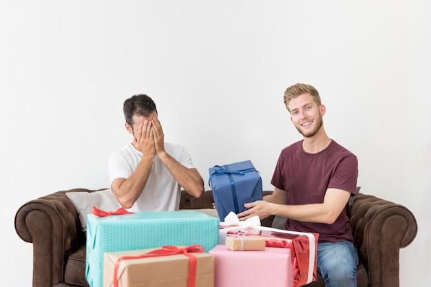 Equipaggi dare il suo contenitore di regalo timido dell'amico contro la parete bianca