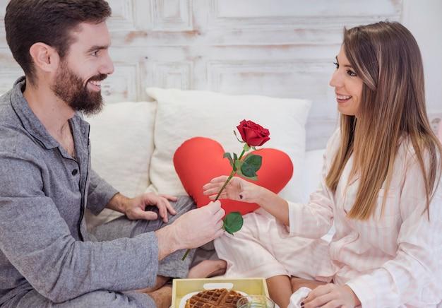 Equipaggi dare la rosa rossa alla donna sul letto