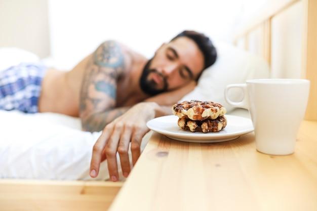 Equipaggi dormire sul letto con alimento dolce e tazza di caffè sopra lo scrittorio di legno