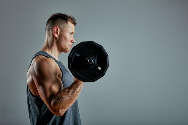 Equipaggi fare l'allenamento posteriore, fila del bilanciere in studio sopra fondo grigio. copia spazio