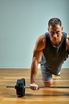 Equipaggi fare l'allenamento posteriore, fila del bilanciere in studio sopra grey