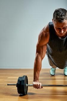Equipaggi fare l'allenamento posteriore, fila del bilanciere sopra la parete grigia. copia spazio