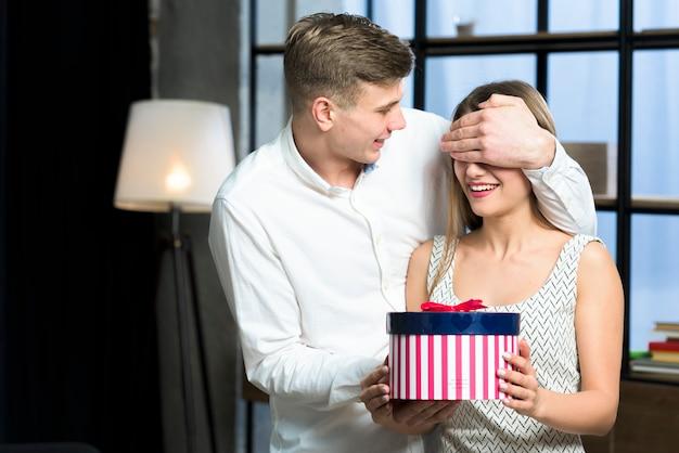Equipaggi gli occhi della copertura della donna con il grande contenitore di regalo