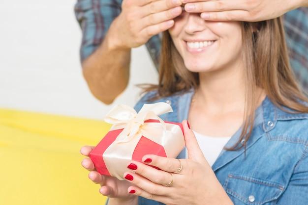 Equipaggi gli occhi della copertura della sua ragazza felice che tiene il regalo del biglietto di s. valentino