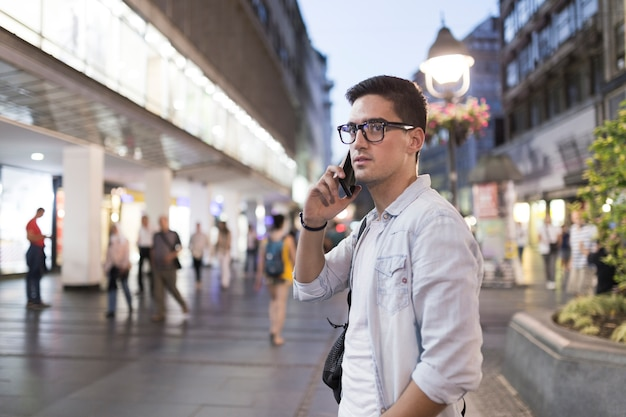 Equipaggi gli occhiali d'uso che parlano sul telefono cellulare