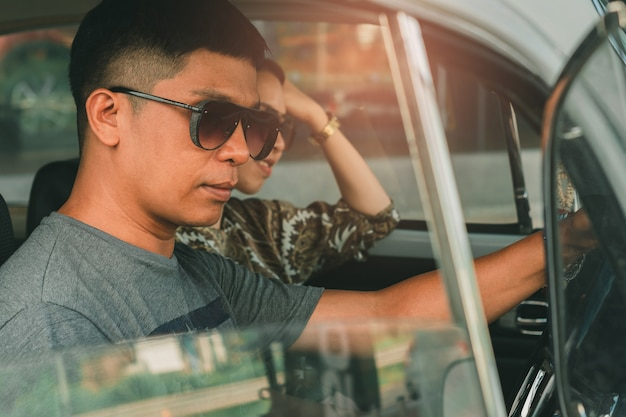 Equipaggi gli occhiali da sole d'uso che guidano l'annata dell'automobile con la femmina sulla via