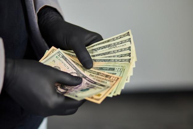 Equipaggi i dollari dei soldi della holding disponibili in guanti medici neri.