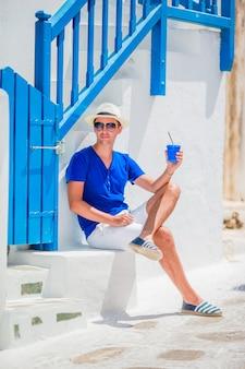 Equipaggi il caffè bevente per andare in villaggio greco tradizionale all'aperto. giovane ragazzo con caffè caldo in caffè all'aperto nella città di mykonos.