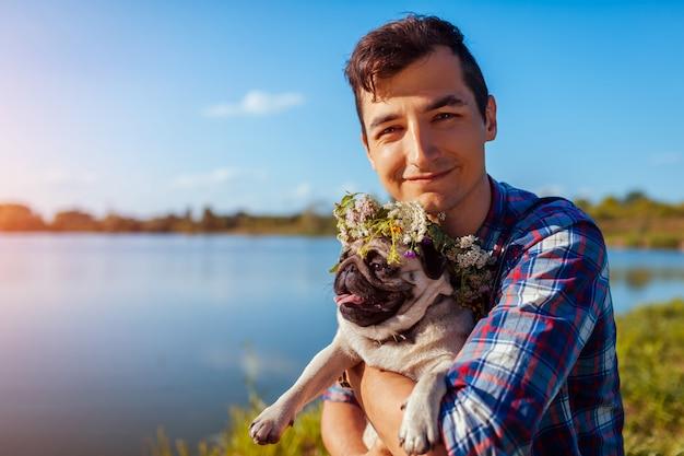 Equipaggi il cane del carlino della tenuta con la corona del fiore sulla testa. uomo che cammina con l'animale domestico dal lago summer
