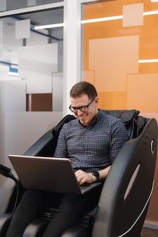 Equipaggi il codice di scrittura mentre si siedono in poltrona nell'ufficio