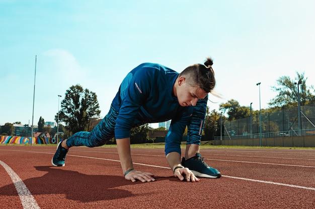 Equipaggi il corridore che allunga le gambe che preparano per l'addestramento di funzionamento sulle piste dello stadio che fanno il riscaldamento