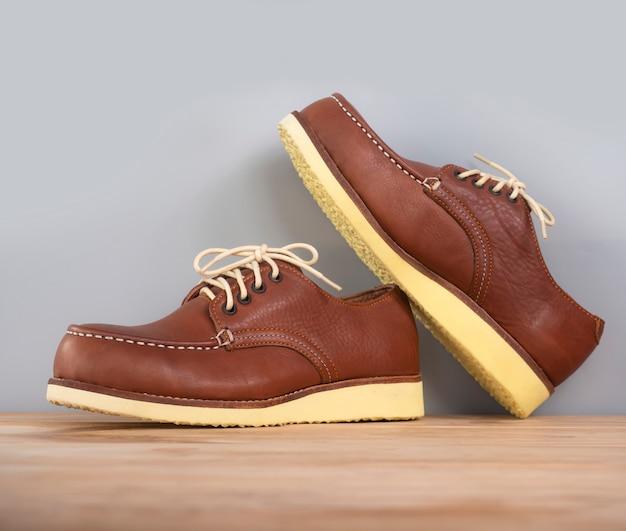 Equipaggi il cuoio marrone delle scarpe di modo su di legno su gray