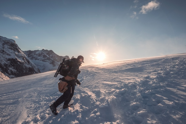 Equipaggi il fotografo che scala sulla montagna nevosa con cielo blu al tramonto
